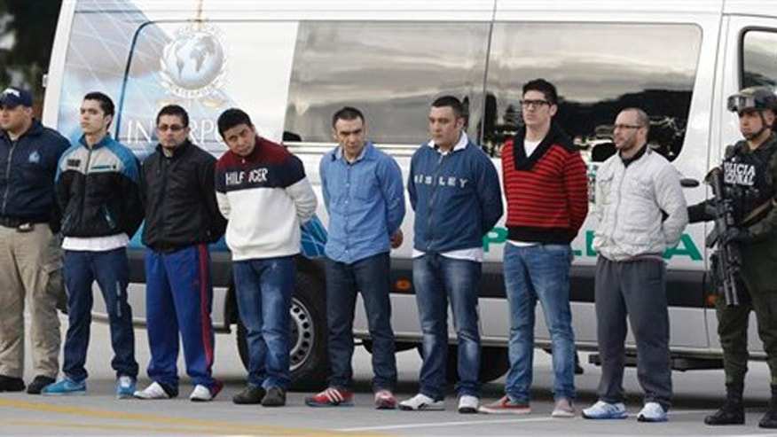 "Police flank seven men accused of murdering a Drug Enforcement Administration agent, during a media presentation at the counter-narcotics base in Bogota, Colombia, Tuesday, July 1, 2014, prior to their extradition to the United States. The men are accused of killing Special Agent James ""Terry"" Watson in an apparent robbery attempt the night of June 20, 2013. (AP Photo/Fernando Vergara)"
