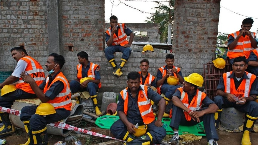 June 30, 2014: Indian rescuers, take a break as they search for workers believed buried in the rubble of a building that collapsed late Saturday during monsoon rains on the outskirts of Chennai, India. (AP)