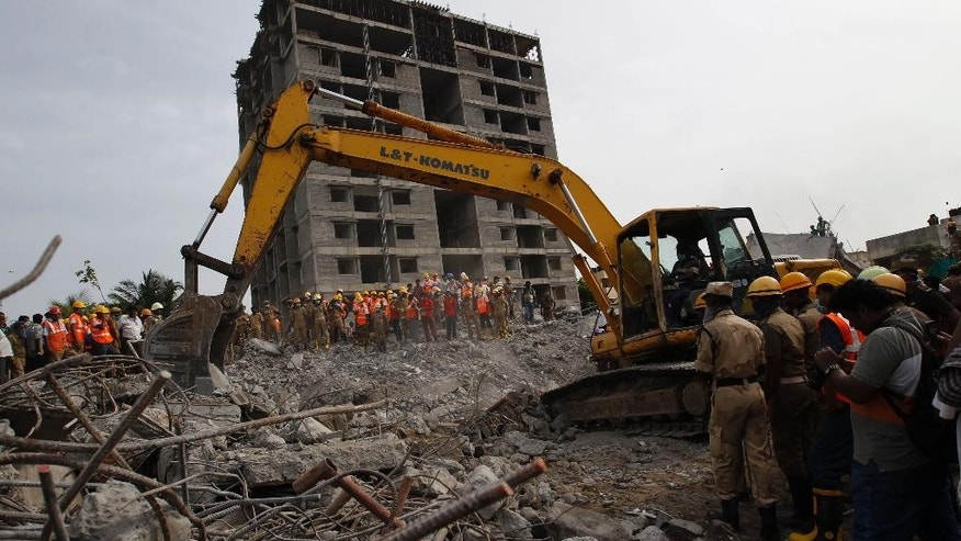 Rescuers, search for workers believed buried in the rubble of a building that collapsed late Saturday during monsoon rains on the outskirts of Chennai, India, Monday, June 30, 2014. Rescuers have pulled at least 41 people from the wreckage, even as seasonal monsoon rains impeded the search. Police said 30 other people are likely still trapped. (AP Photo/Arun Sankar K)