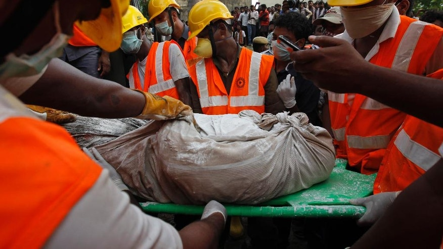 Rescuers, carry a worker's body they pulled out from the rubble of a building that collapsed late Saturday during monsoon rains on the outskirts of Chennai, India, Monday, June 30, 2014. Rescuers have pulled at least 41 people from the wreckage, even as seasonal monsoon rains impeded the search. Police said 30 other people are likely still trapped. (AP Photo/Arun Sankar K)