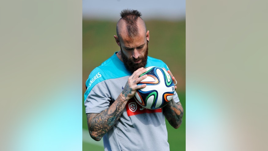 FILE - In this June 19, 2014, file photo, Raul Meireles grabs the ball during a training session of Portugal in Campinas, Brazil.  Meireles' Mohawk has been compared to the one sported by Robert De Niro in 'Taxi Driver.' His thick beard and all-over body tattoos add to his scary-looking appearance. (AP Photo/Paulo Duarte, File)