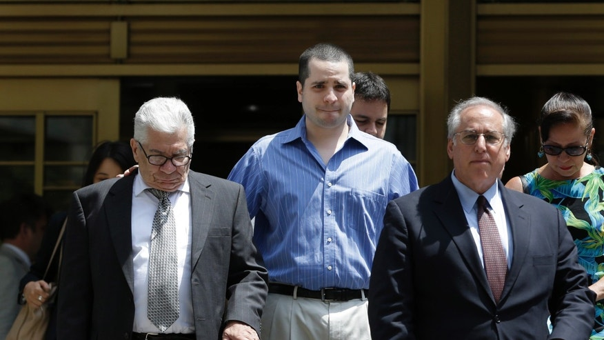 GIlberto Valle, center, leaves Manhattan federal court in New York in New York on Tuesday, July 1, 2014. A federal judge overturned the conviction of the former New York City police officer accused of plotting to kidnap, kill and eat young women. (AP Photo/Seth Wenig)