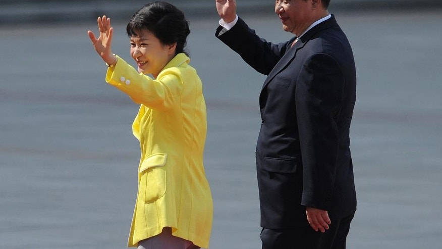 FILE - In this Thursday, June 27, 2013 file photo, South Korean President Park Geun-hye, left, and her Chinese counterpart Xi Jinping wave during a welcoming ceremony outside the Great Hall of the People in Beijing. Xi Jinping's first visit to the Korean Peninsula as China's president is to Seoul, not Pyongyang, meaning that North Korea's best friend has snubbed it for its most bitter rival. A flurry of recent rocket and missile tests, the latest on Wednesday, has made the North's displeasure crystal clear.  (AP Photo/Wang Zhao, Pool, File)