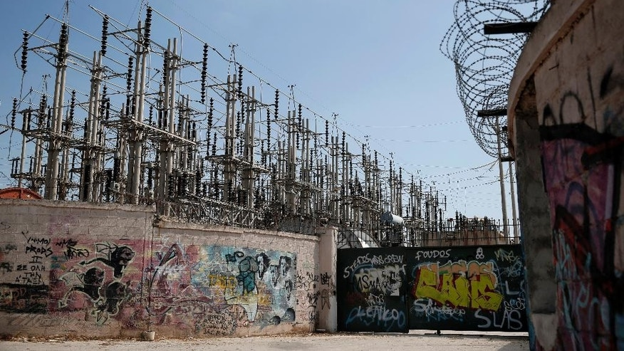 Graffiti is painted on walls and the entrance of an electric station of Public Power Corporation (PPC) in Athens, on Wednesday, July 2, 2014. PPC workers are threatening with rolling strikes to protest government plans to sell a stake in the company to private investors. The conservative-led government is warning that a protracted strike could lead to blackouts at the height of Greece's key tourist season, and has said it could try to force PPC workers back to work through a mobilization order. (AP Photo/Petros Giannakouris)