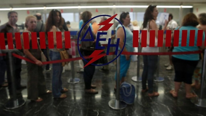 People queue to pay their electricity bills at a Public Power Company office in central Athens, Wednesday, July 2, 2014. PPC workers are threatening with rolling strikes to protest government plans to sell a stake in the company to private investors. The conservative-led government is warning that a protracted strike could lead to blackouts at the height of Greece's key tourist season, and has said it could try to force PPC workers back to work through a mobilization order. (AP Photo/Petros Giannakouris)