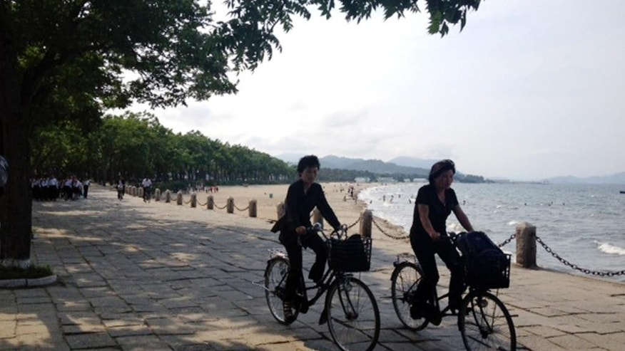 In this Monday, June 16,2014 photo taken with smartphone camera, North Koreans ride on bicycles along a beach in Wonsan, North Korea. Wonsan, a sleepy port on North Korea's east coast, is gearing up for a busy summer - and, if talks with Japan go as North Korea hopes, maybe a return to livelier days. (AP Photo/Eric Talmadge)