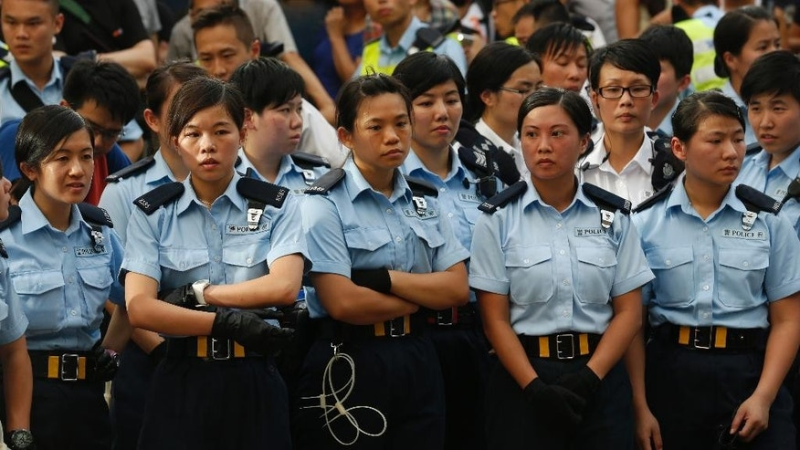 Policewomen stand next to the protesters during a peaceful sit-ins protest on a street in the financial district in Hong Kong Wednesday, July 2, 2014, following a huge rally to show their support for democratic reform and oppose Beijing's desire to have the final say on candidates for the chief executive's job. (AP Photo/Kin Cheung)