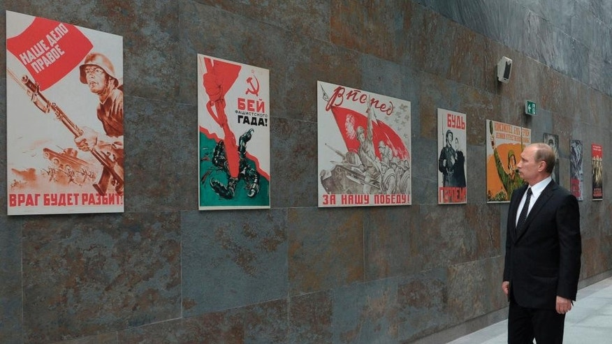Russian President Vladimir Putin looks at Soviet World War II era posters  as he visits a WWII history museum in Minsk, Belarus, Wednesday, July 2, 2014. President Putin arrived in Minsk to attend celebrations marking the 70th anniversary of Minsk's liberation from Nazi's troops during WWII. (AP Photo/RIA-Novosti, Alexei Druzhinin, Presidential Press Service)