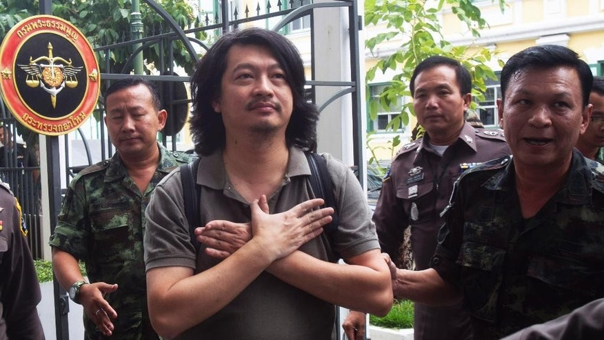FILE - In this Thursday, June 12, 2014 file photo, Sombat Boonngam-anong gestures a sign of freedom while arriving at the military court in Bangkok, Thailand. Sombat was released from police custody Tuesday, July 1, 2014, on conditions that he not incite unrest or travel overseas without permission from authorities after posting a 300,000 baht ($9,250) bail, said Police Col. Kittirat Noiponthong. (AP Photo/Sakchai Lalit, File)