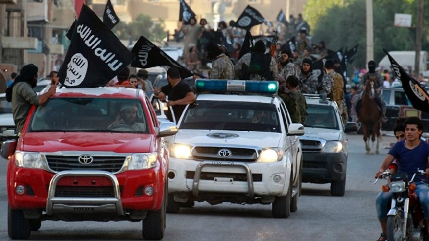 "June 30, 2014: Militant Islamist fighters waving flags, travel in vehicles as they take part in a military parade along the streets of Syria's northern Raqqa province. The fighters held the parade to celebrate their declaration of an Islamic ""caliphate"" after the group captured territory in nearby Iraq, a monitoring service said."