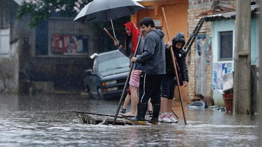 A family uses a raft to navigate the flooded streets in the Tacumbu neighborhood of Asuncion, Paraguay, Friday, June 27, 2014. Floods caused by torrential rains have forced the evacuation of 200,000 people living near the Paraguay and Parana rivers. (AP Photo/Jorge Saenz)