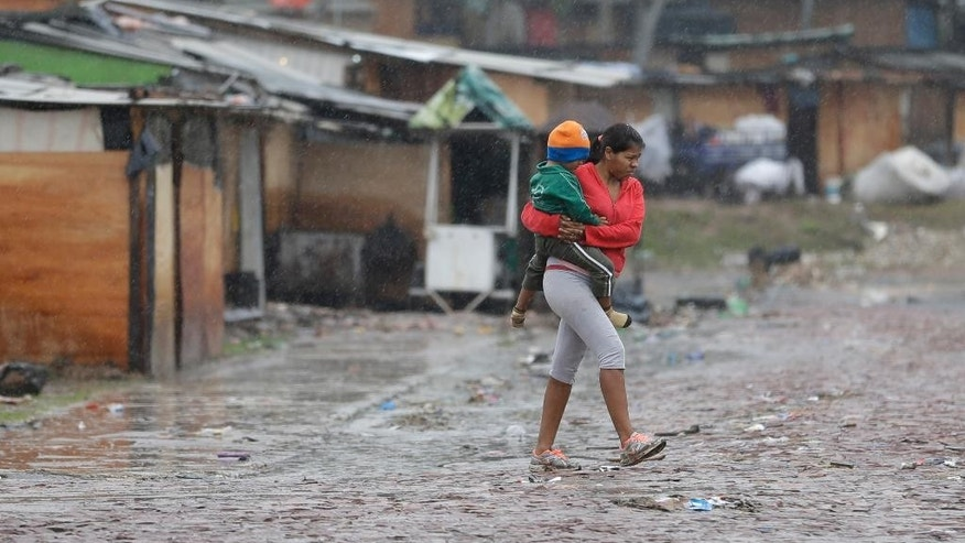 A woman carries her baby under the rain in a camp set up by people displaced by flooding in Asuncion, Paraguay, Friday, June 27, 2014. Floods caused by torrential rains have forced the evacuation of 200,000 people living near the Paraguay and Parana rivers. (AP Photo/Jorge Saenz)