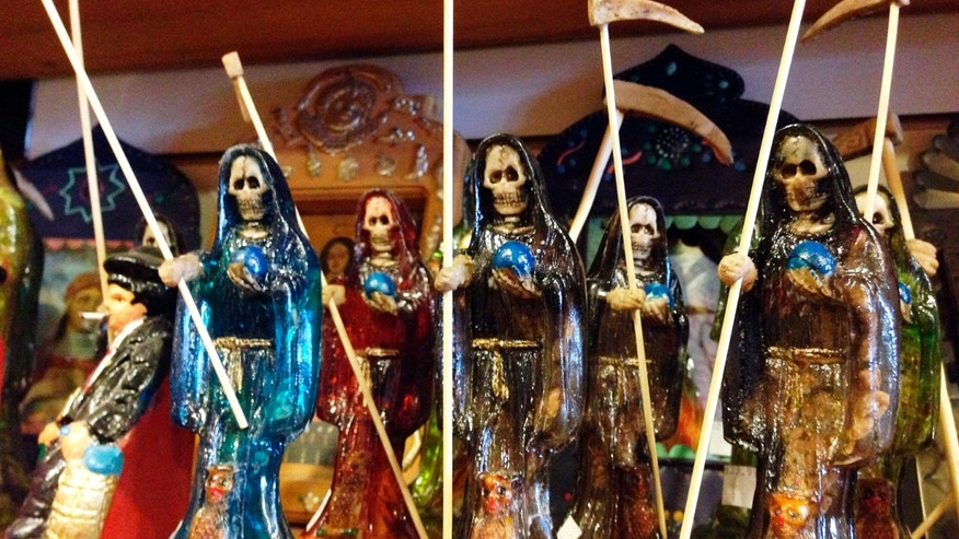 FILE - In this Feb. 13, 2013 file photo, statues of La Santa Muerte, an underworld saint most recently associated with the violent drug trade in Mexico, are shown at the Masks y Mas art store in Albuquerque, N.M. (AP Photo/Russell Contreras, File)