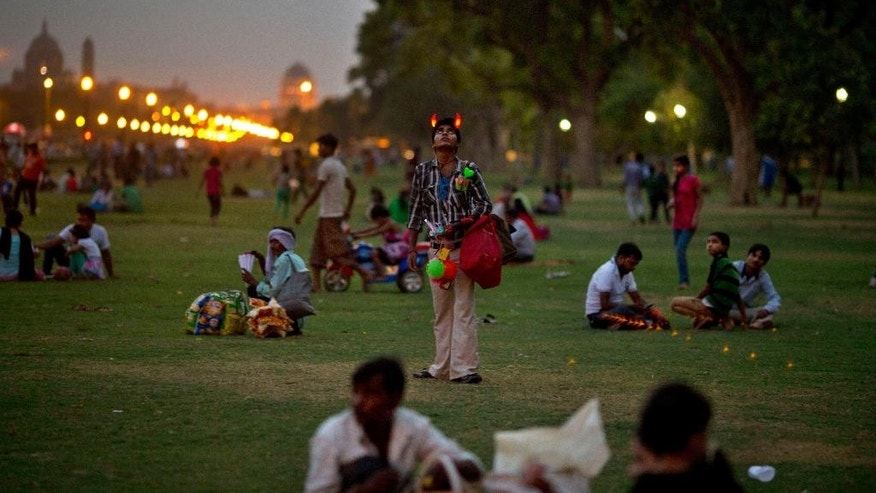 In this Monday, June 30, 2014 photo, a man selling trinkets looks up to watch a toy helicopter descend at the lawns of India Gate park in New Delhi, India. With temperatures reaching 100 degrees every day, India Gate, the colonial park in the center of New Delhi is a temperate escape for the middle-class and working-class - the kind of people who don't have their own backyards, and can't afford air-conditioners and generators during power blackouts. It's a safe place for families to gather, to picnic, to buy balloons and pink cotton candy and watch dancing monkeys. (AP Photo/Saurabh Das)