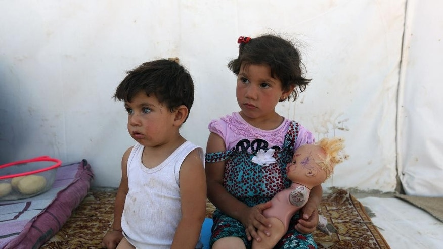 June 29, 2014: Syrian refugee Youmna, 4, right, and her brother Ammar, 3, sit outside their tent at a Syrian refugee camp in the eastern town of Marj in Bekaa valley, Lebanon.