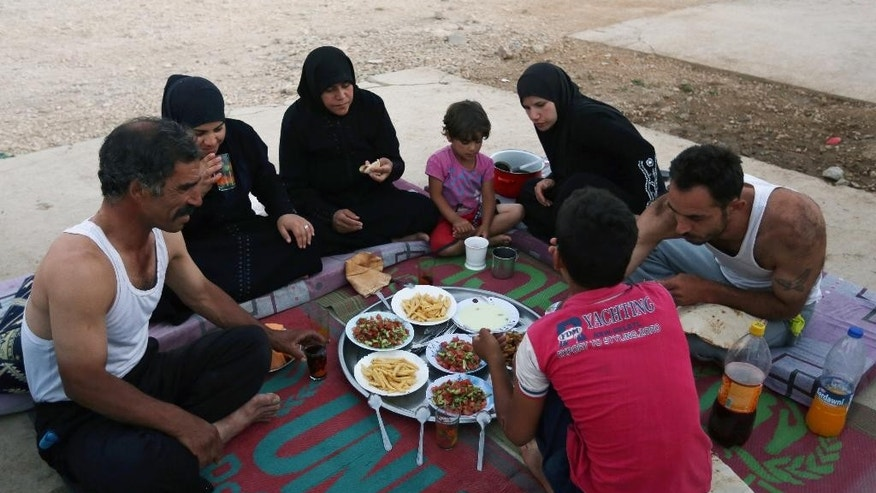 June 29, 2014: Syrian refugee family members, who fled their home from Syria, break their fasting outside their tent at a Syrian refugee camp in the eastern town of Marj in Bekaa valley, Lebanon. Across a wide belt that stretches halfway around the globe, the world's estimated 1.6 billion Muslims mark the beginning of Ramadan this weekend.