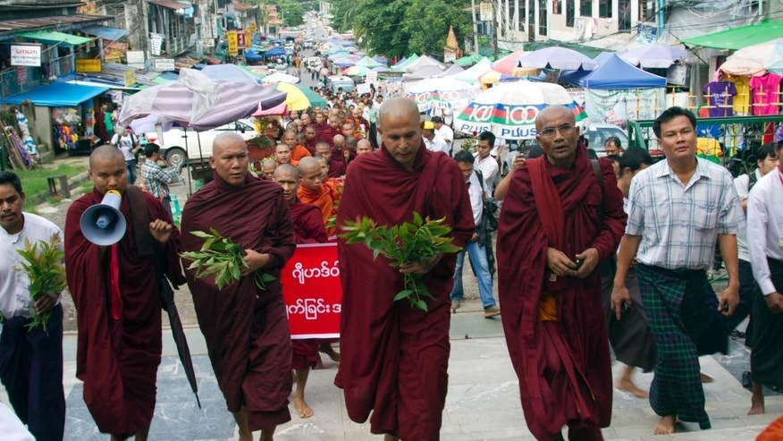 Myanmar Buddhist monks march during a rally against recent violence in central Myanmar, Friday, July 4, 2014, in Yangon, Myanmar. Myanmar's second-largest city is quiet Friday after an overnight curfew restored calm following two nights of violent rampages by extremist Buddhists. Authorities imposed the curfew in Mandalay late Thursday after attacks on minority Muslims left two people dead and 14 injured, raising fears that ethnic violence that has plagued the country for two years may escalate again.  (AP Photo/Khin Maung Win)