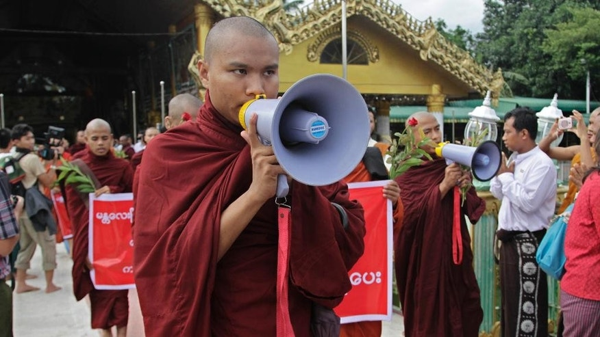 A Myanmar Buddhist monk speaks over a public-address system during a rally against recent violence in central Myanmar, Friday, July 4, 2014, in Yangon, Myanmar. Myanmar's second-largest city is quiet Friday after an overnight curfew restored calm following two nights of violent rampages by extremist Buddhists. Authorities imposed the curfew in Mandalay late Thursday after attacks on minority Muslims left two people dead and 14 injured, raising fears that ethnic violence that has plagued the country for two years may escalate again.  (AP Photo/Khin Maung Win)