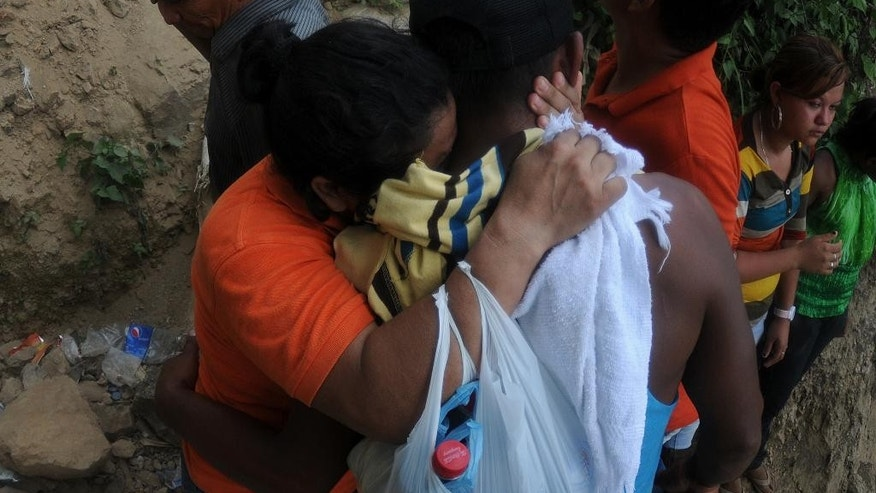 Relatives of 11 miners trapped inside a gold mine after a landslide, cry while the rescue operation continues in San Juan Arriba, Choluteca in southern Honduras, Thursday, July 3, 2014. More than 300 Red Cross volunteers, firefighters and people who live near the mine in the town of El Corpus were digging by hand in an effort to reach the miners. (AP Photo/Fernando Antonio)
