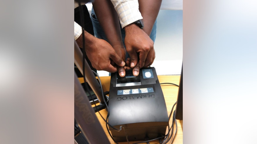 "In this June 10, 2014, photo, a Dominican employee takes the fingerprints of a Haitian immigrant for the ""regularization process"" of foreigners living in the Dominican Republic, in Santo Domingo, Dominican Republic. Since the program opened on June 2, and with a deadline early next year before the Dominican government says it will begin deporting migrants who don't have authorization to be in the country, only a tiny fraction of the applicants have managed to show sufficient documentation from their homeland to secure legal status, officials say. (AP Photo/Ezequiel Abiu Lopez)"