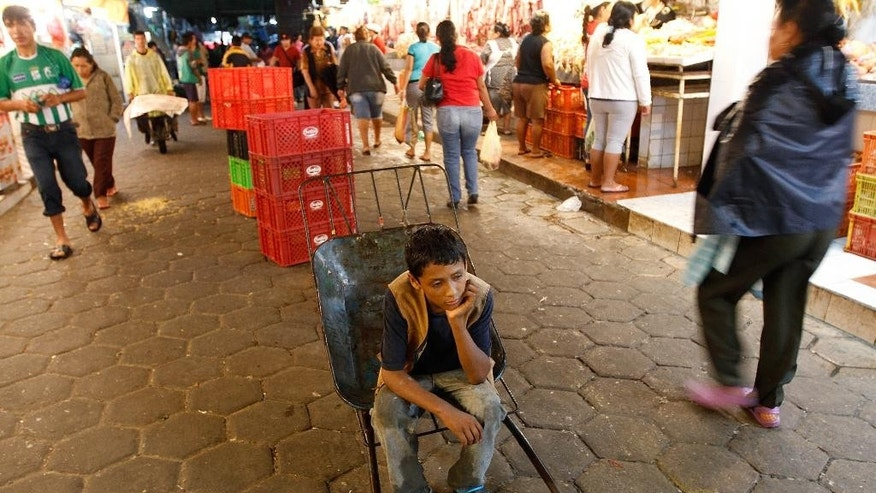 In this Jan. 29, 2014 photo, a 12-year-old boy who did not want to give his name rests as he works as a porter at the El Abasto market in Santa Cruz, Bolivia. Bolivia's Congress has passed legislation to allow children as young as age 10 to work legally as long as the work does not interfere with their education and is performed for a family enterprise. The legislation, passed late July 2, 2014, would make Bolivia the first country to make work by 10-year-olds legal, and is expected to be signed into law shortly by President Evo Morales. (AP Photo/Juan Karita)