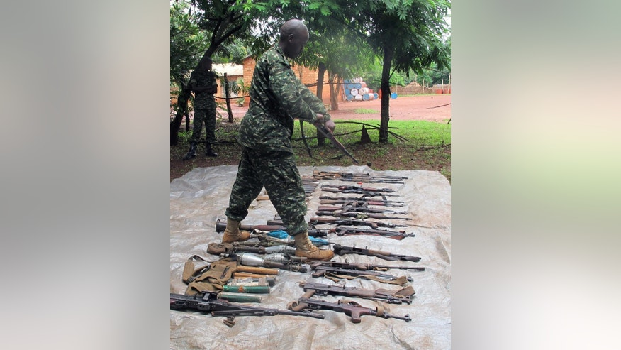 In this Wednesday, June 25, 2014 photo, a Ugandan soldier displays weapons, including machine guns and rocket-propelled grenade launchers, that have recently been seized from members of the Lord's Resistance Army rebel group in Central African Republic. African troops hoped the latest defector from the Lord's Resistance Army rebel group would have something fresh to say about the possible whereabouts of the infamous warlord Joseph Kony. But Sam Opio, a senior rebel commander who defected last week, shook his head and said he hadn't seen rebel leader Kony since 2010. And he is not alone. All recent defectors have denied seeing or communicating with Kony in the last few years, complicating the work of U.S.-backed Ugandan troops who are hunting down rebels in the dense, often-impenetrable jungles of Central Africa. An Associated Press reporter recently trailed soldiers tracking a very small group of rebels. (AP Photo/Rodnet Muhumuza)
