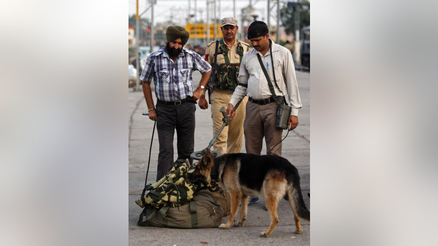 Security officers, along with a sniffer dog, inspect luggage at a railway station in Jammu, india, Thursday, July 3, 2014. Security has been beefed up ahead of Indian prime minister Narendra Modi's visit to the state of Jammu and Kashmir, Police said. (AP Photo/Channi Anand)