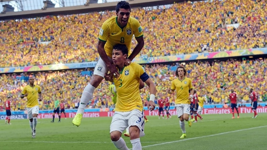Brazil's Thiago Silva, bottom, celebrates with Paulinho after scoring the opening goal during the World Cup quarterfinal soccer match between Brazil and Colombia at the Arena Castelao in Fortaleza, Brazil, Friday, July 4, 2014. (AP Photo/Manu Fernandez)