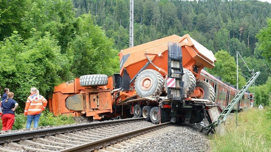 The wreckage of a truck stands on the track after a collision with a train near Talhausen south of Stuttgart, Friday July 4, 2014.  A train has collided with a truck at a railway crossing in southwestern Germany, leaving 33 people injured-  four of them seriously.  A police statement said that the truck, a low-loader carrying a skip, got stuck on the crossing for reasons that remain unclear.  The train driver braked sharply but was unable to avoid the truck, which was pushed about 50 meters (165 feet) along the track.  The truck driver and a passenger were lightly injured. Thirty-one people aboard the train were injured.   (AP Photo/dpa, Bernd Weißbrod)