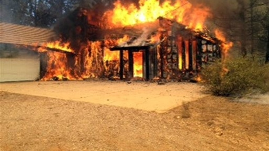 In this still frame from video provided by KNSD-TV, a home is fully involved in flames as crews scrambled to corral a wildfire that burned two homes near the San Diego County mountain town of Julian in Southern California Thursday, July 3, 2014. The blaze erupted around 10:30 a.m. and prompted the mandatory evacuation of 200 homes. Firefighters attacked the 150-acre blaze in the air and on the ground. The fire destroyed two homes and an outbuilding and was 15 percent contained at nightfall, state fire Capt. Kendal Bortisser said. (AP Photo/KNSD-TV)