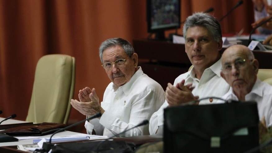 Cuba's President Raul Castro, from left, Vice President Miguel Diaz-Canel and Vice President Jose Ramon Machado Ventura, applaud during the third regular session of the eighth legislature, at the National Assembly in Havana, Cuba, Saturday, July 5, 2014. As is tradition, Cuba's parliament opened the session with the chair normally occupied by Fidel Castro, left empty. (AP Photo/Ismael Francisco, Cubadebate)