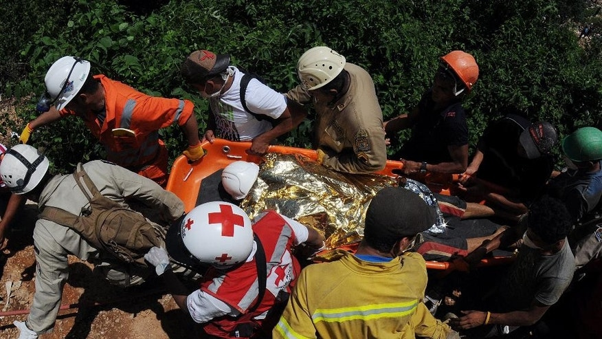 Rescue workers carry a miner who was trapped in a gold mine after a collapse in San Juan Arriba, Choluteca in southern Honduras, Friday, July 4, 2014. Three miners were rescued Friday after spending more than two days trapped following a collapse at a small, wildcat gold mine. Eight others remain missing. (AP Photo/Fernando Antonio)