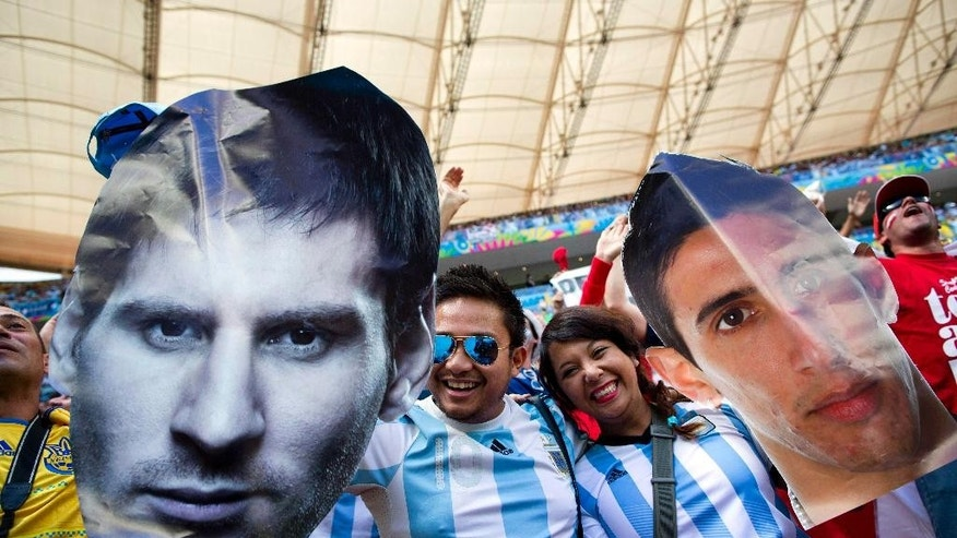 Fans of Argentina's national soccer team hold face cutouts of Lionel Messi, left, and Angel Di Maria, during the World Cup quarterfinal match between Argentina and Belgium at the Estadio Nacional  in Brasilia, Brazil, Saturday, July 5, 2014. (AP Photo/Rodrigo Abd)