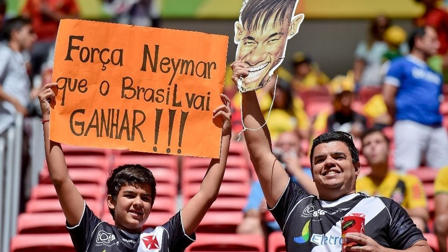 Spectators hold up a mask of Brazil's Neymar and a sign that translates as 'Have strength Neymar. Brazil will win', before the World Cup quarterfinal soccer match between Argentina and Belgium at the Estadio Nacional in Brasilia, Brazil, Saturday, July 5, 2014. (AP Photo/Martin Meissner)