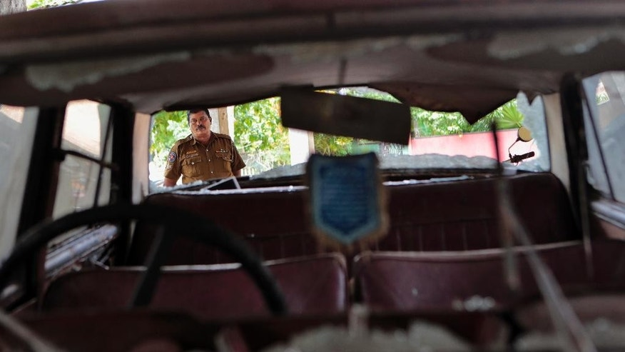 In this Wednesday, June 25, 2014 photo, a Sri Lankan police officer inspects a car that was vandalized during clashes between Buddhists and Muslims in Darga Town, in Aluthgama about 50 kilometers (31 miles) south of Colombo, Sri Lanka. The onslaught by the Bodu Bala Sena, a hardline Buddhist group that has gained thousands of followers in recent years, killed two Muslims and injured dozens more last month in the worst religious violence Sri Lanka has seen in decades. (AP Photo/Eranga Jayawardena)