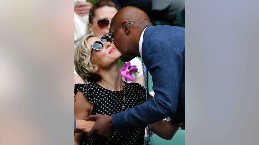 U.S actor Samuel L. Jackson, right, kisses Elsa Pataky as he arrives in the Royal Box prior to the men's singles final between Roger Federer of Switzerland and Novak Djokovic of Serbia on centre court at the All England Lawn Tennis Championships in Wimbledon, London, Sunday July 6, 2014. (AP Photo/Ben Curtis)