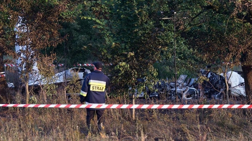 A firefighter officer examines the crash site of a plane near the village of Topolow in Poland, Saturday, July 5, 2014. The small Piper Navajo aircraft carrying parachutists crashed and burst into flames shortly after takeoff, killing several people and injuring at least one. (AP Photo)