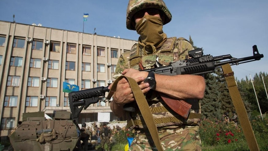 July 5, 2014: An Ukrainian government army soldier stands in front of the government building with a Ukrainian flag on the roof in the city of Slovyansk, Donetsk Region, eastern Ukraine. (AP)