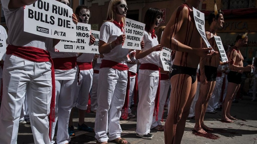 Anti-bullfighting demonstrators, with their bodies covered with blood, right, protest against the bull runs on the Ayuntamiento Square in Pamplona northern Spain, Saturday, July 5, 2014. On July 6, the San Fermin festival will begin with the ''txupinazo'' , the opening ceremony with people participating in bull runs, music and dance, through the old street of the city. (AP Photo/Alvaro Barrientos)