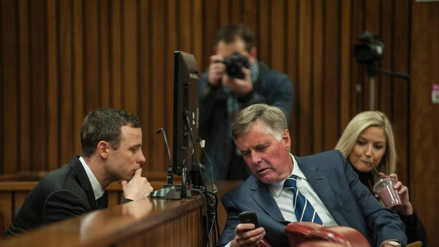 July 7, 2014 - Oscar Pistorius, left, talks with a defense team member in court in Pretoria at his ongoing murder trial for the shooting death of his girlfriend Reeva Steenkamp in Feb., 2013. The chief prosecutor, Gerrie Nel has challenged the credibility of a physician, who testified that the athlete has an anxious nature linked to his disability and could not be objective about the double-amputee runner because he had treated Pistorius over many years and traveled with him extensively.