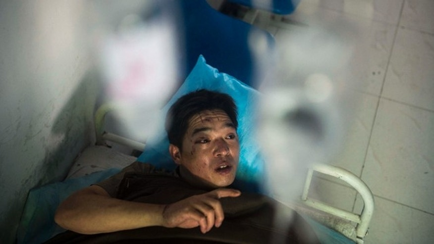 July 6, 2014: In this photo released by China's Xinhua News Agency, miner Duan Xukang receives a treatment at a hospital in Fukang City, northwest China's Xinjiang Uygur Autonomous Region, after being rescued following a gas explosion at a coal mine. (AP Photo/Xinhua, Jiang Wenyao)