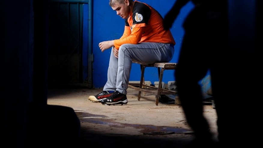In this Jan 18, 2014, photo, Villa Clara's pitcher Diosdani Castillo takes a break after a training session at the Latinamerican stadium in Havana, Cuba. Cuban authorities say Castillo, as well as the team's other pitcher Yasmany Hernandez Romero, will no longer play for the local club which won the championship last season, after they allegedly attempted to defect. (AP Photo/Franklin Reyes)