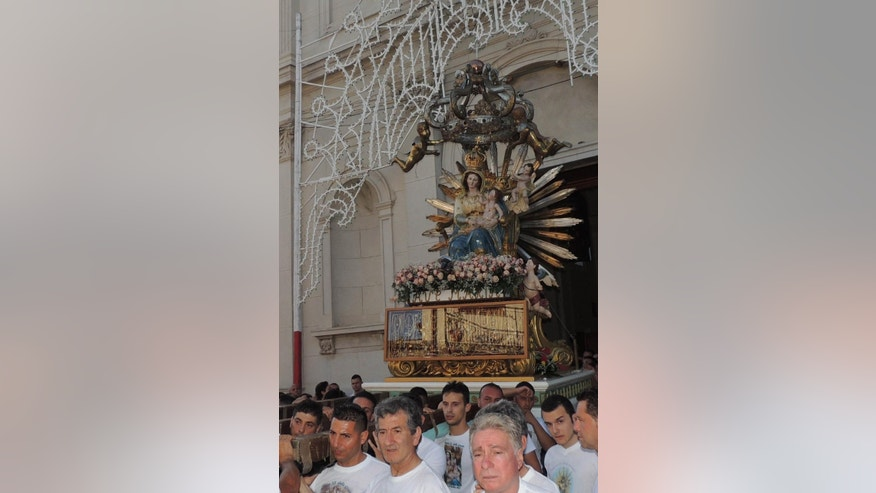 In this Monday,  July 2, 2014 photo made available Sunday July 6, 2014, a Madonna statue is carried during religious procession in Oppido Mamertina, Calabria region, Southern Italy. In apparent defiance of Pope Francis, the church procession has detoured from its route to honor a convicted mobster under house arrest.  Interior Minister Angelino Alfano on Sunday denounced the tribute in Oppido Mamertina, a Calabrian town and 'ndrangheta crime syndicate stronghold, as ''deplorable and disgusting.'' He praised three Carabinieri policemen who abandoned the procession in disapproval. (AP Photo/Toni Condello)
