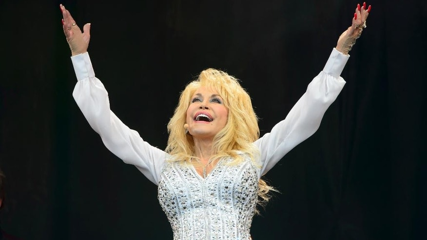 "FILE - In this Sunday, June 29, 2014 file photo, U.S singer Dolly Parton performs at Glastonbury music festival, England. Dolly Parton wants to take an unlikely fan home with her. Dolly"" the dog was found abandoned at Britain's Glastonbury music festival in one of the thousands of tents which spring up every year at the countryside festival, famous for rain and mud as much as its star performers.  After Parton wowed more than 150,000 people she heard about the dog with the fluffy white coat and offered to adopt it. ""I will take the dog home to America if nobody claims her,"" she said in a statement Sunday, July 6, 2014.  (Photo by Jonathan Short/Invision/AP, File)"
