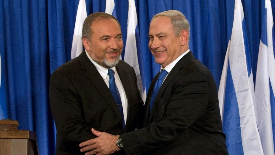 "FILE - In this Oct. 25, 2012 file photo, Israeli Prime Minister Benjamin Netanyahu, right, and  Foreign Minister Avigdor Lieberman shake hands in front the media after giving a statement in Jerusalem.  Israel's foreign minister says he is ending his political alliance with Prime Minister Benjamin Netanyahu. Lieberman told a news conference Monday, July 7, 2014 that he and Netanyahu have ""substantial"" differences. Despite the decision, Lieberman's Yisrael Beitenu party will remain in the governing coalition, and Lieberman will remain as foreign minister. (AP Photo/Bernat Armangue, File)"