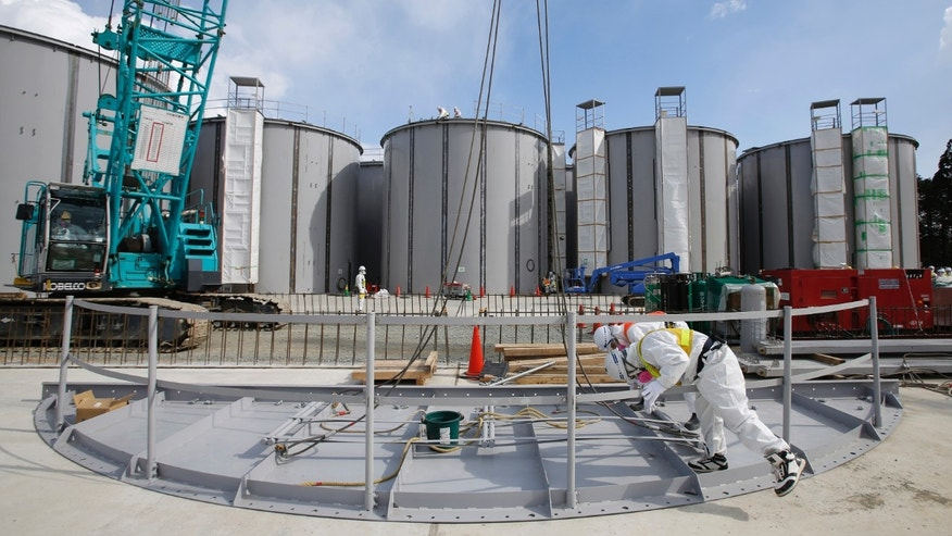 March 10, 2014 - FILE photo of men wearing protective suits and masks work in front of welding storage tanks for radioactive water, under construction at TEPCO's tsunami-crippled Fukushima Daiichi nuclear power plant in Fukushima prefecture, Japan.