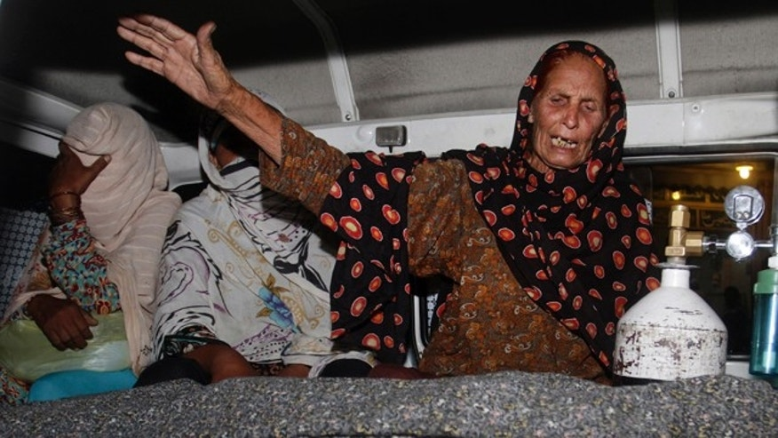 FILE - In this Tuesday, May 27, 2014 file photo, a family member of a pregnant woman who was stoned to death by a mob wails over her body in an ambulance at a local hospital in Lahore, Pakistan. (AP Photo/K.M. Chaudary, File)