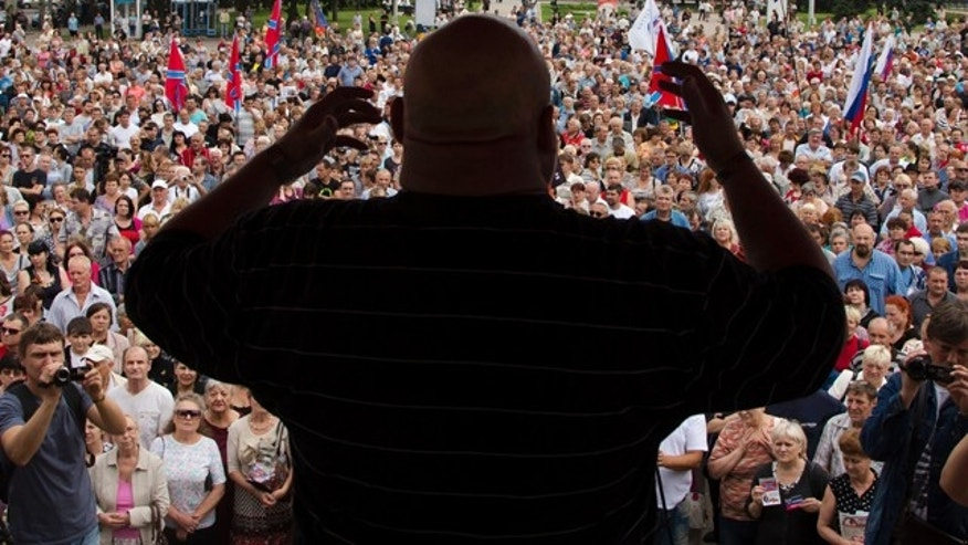 July 6, 2014: People listen to a pro-Russian activist during a pro-Russian meeting in the city of Donetsk, eastern Ukraine. (AP Photo/Dmitry Lovetsky)