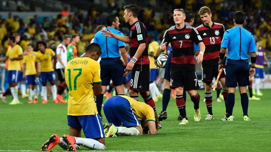 Brazil players sink to their knees after the World Cup semifinal soccer match between Brazil and Germany at the Mineirao Stadium in Belo Horizonte, Brazil, Tuesday, July 8, 2014. Germany won the match 7-1. (AP Photo/Martin Meissner)