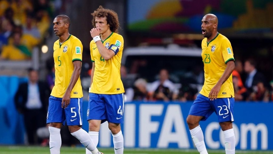 Brazil's Fernandinho, David Luiz and Maicon, from left, walk over the pitch after Germany scored their fifth goal during the World Cup semifinal soccer match between Brazil and Germany at the Mineirao Stadium in Belo Horizonte, Brazil, Tuesday, July 8, 2014. (AP Photo/Frank Augstein)